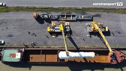 Binnenschiff und Schwertransport mit Tiefbett beim Umsetzen der Fracht mit zwei Kränen aus der Vogelperspektive.
