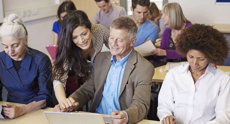 Erwachsene Studenten in Weiterbildung mit Lehrerin.