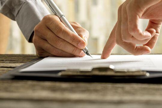 Hand mit Stift beim Unterschreiben
